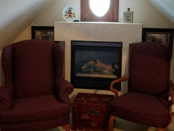 two burgundy chairs on either side of fireplace