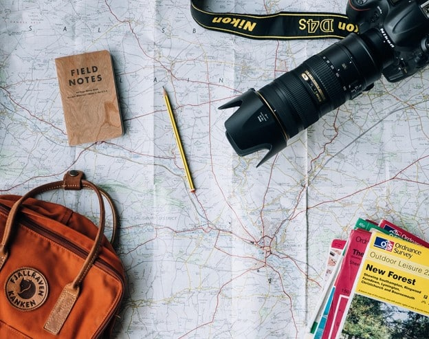 Trip planning items including a stack of field guides, a notebook with pencil, camera with zoom lens and a brown leather travel satchel lie on top of a spread out map.
