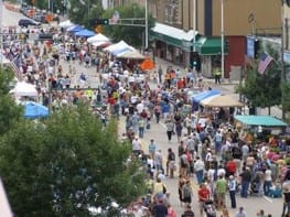 Street Fair Scene with a crowded street of people visiting tent top booths