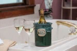Wine bottle in green ceramic wine chiller and half-full glasses of white wine on edge of beautiful bathtub