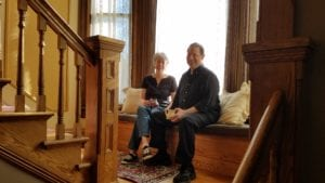 A couple enjoying coffee, seated on the window-seat in the grand staircase
