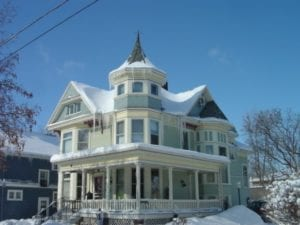 Snow covered Victorian House with turret and wrap-around porch