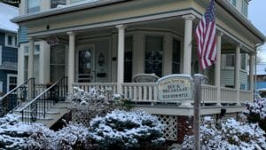 Snow topped shrubbery in front of a Victorian-style wrap-around porch with Franklin Street Inn sign in foreground