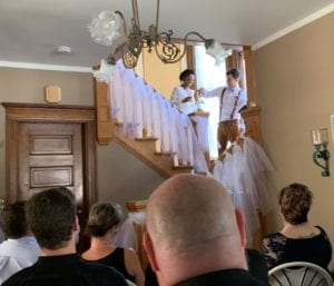 Blake and Helen perform sand unity ceremony at wedding. Setting is couple on grand staircase with family members in foreground looking on.