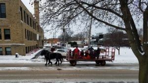 Horse drawn wagon full of people; snow on ground; church in background