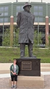 Lori standing in front of Vince Lombardi statue with Lambeau Field football stadium in background