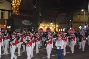 Marching band at nighttime Christmas parade, White slacks with red vests and wearing red christmas hats