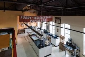 White room with white cabinets and black lab-type counter-tops beneath brown paper sign with white lettering reading Purdy-Weissenborn Paper Lab