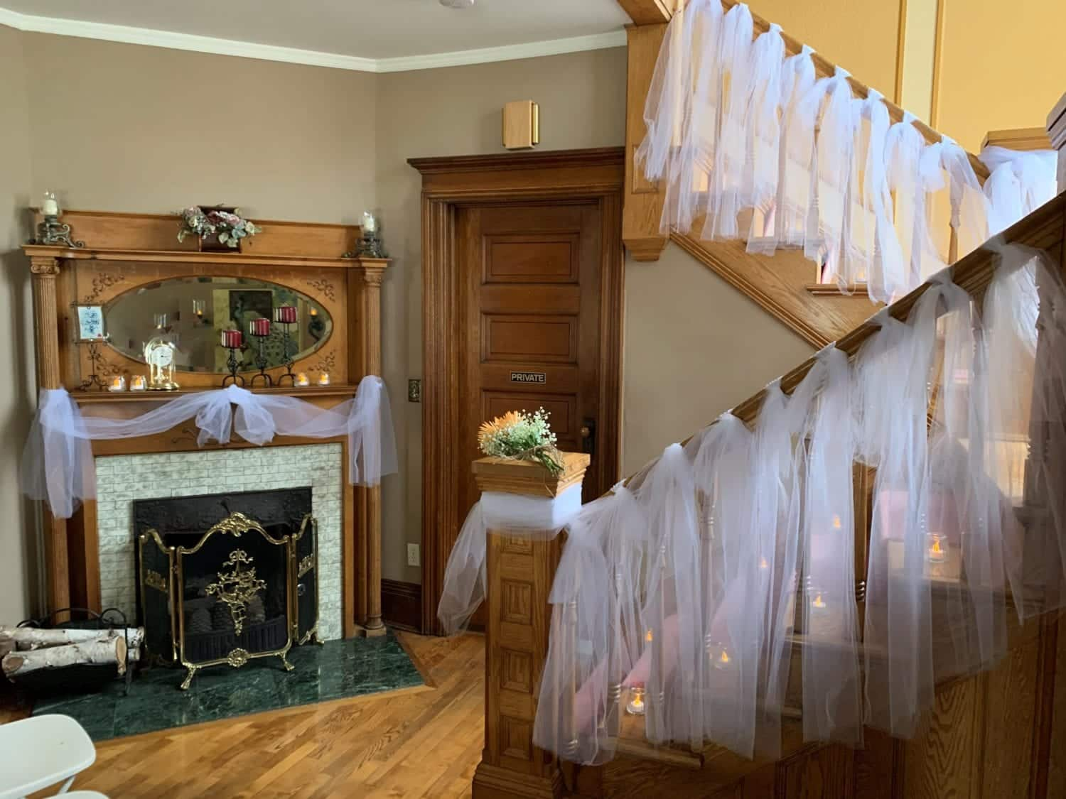 Beautiful wooden Grand staircase and fireplace mantle decorated in white tulle fabric for a wedding