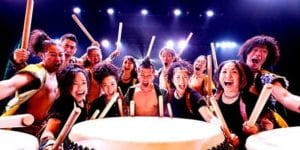 An array of excited people with large drum sticks surrounding several large drums.