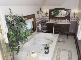 bathroom with bubble bath, wine perched on side of tub, sink in antique furniture