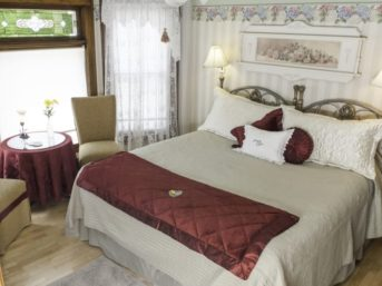Bed in Lawrence Room accented with burgundy decor