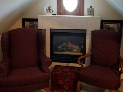 two red chairs on either side of fireplace