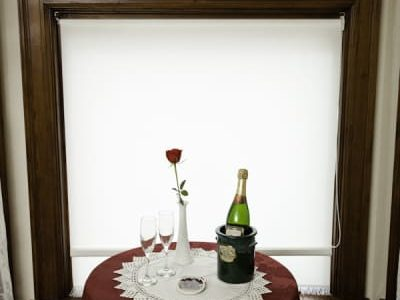 table with red tablecloth, rose and wine in front of window