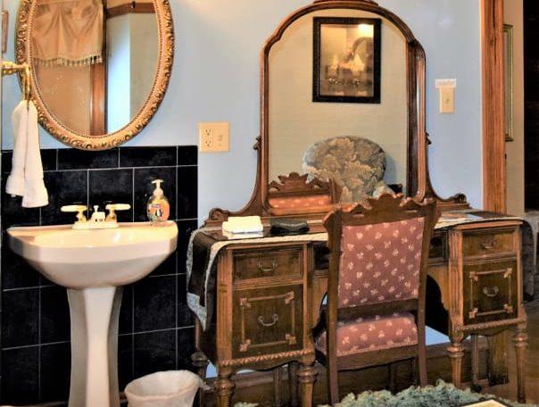 Bathroom in Rhodes Room with antique dresser and pedestal sink