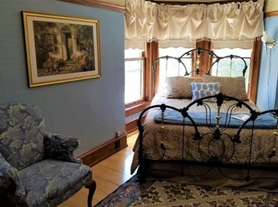 Iron bed set in turret of windows in Rhodes Room