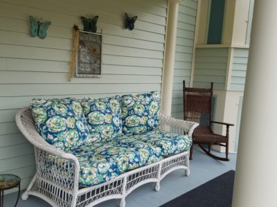 porch with white wicker sofa and brown wicker rocker