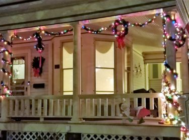 Front porch of Franklin Street Inn decorated with lights at Christmas