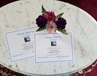 2 gift certificates for inn on table with flowers