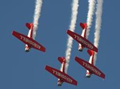 flying aerobatic planes against bright blue sky