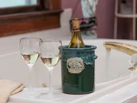 bottle and glasses of wine perched on side of tub