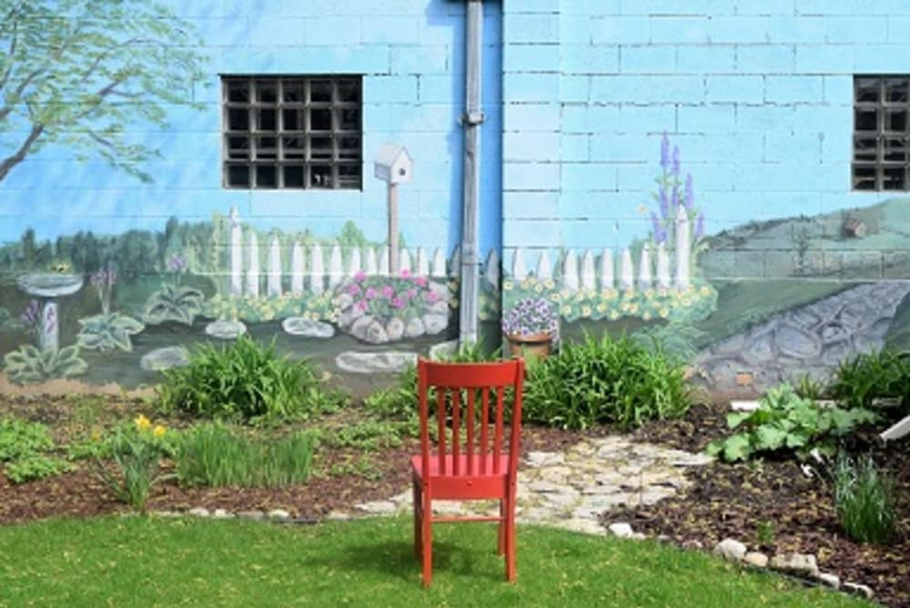 red chair looking at garden with garden scene murial on wall