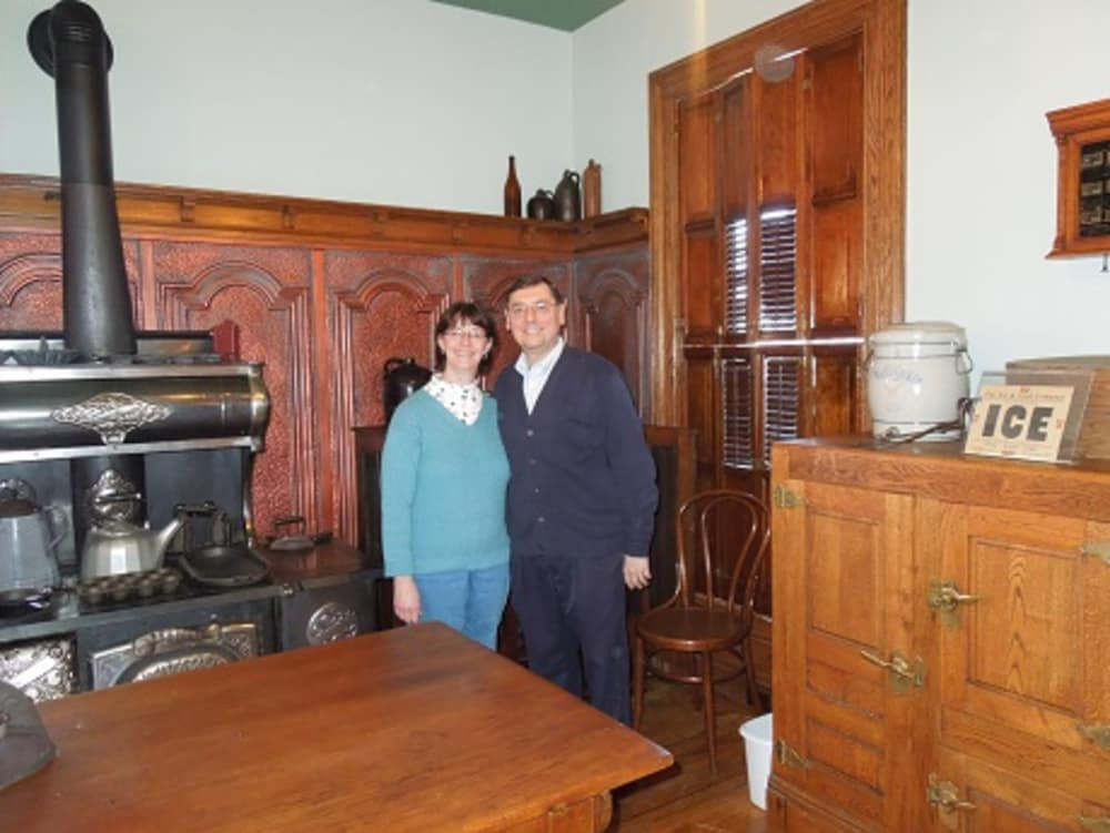 smiling innkeepers next to antique stove