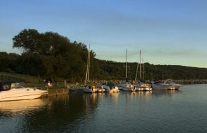 sailboats and speed boats docked along shore of lake