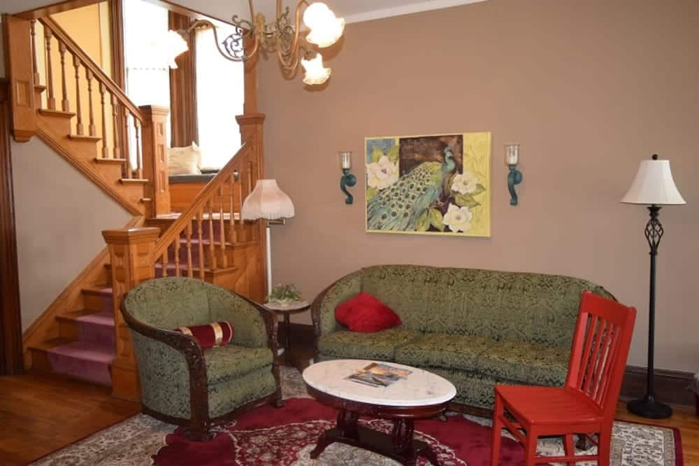 red chair sitting in entry way of inn next to green sofa and chair