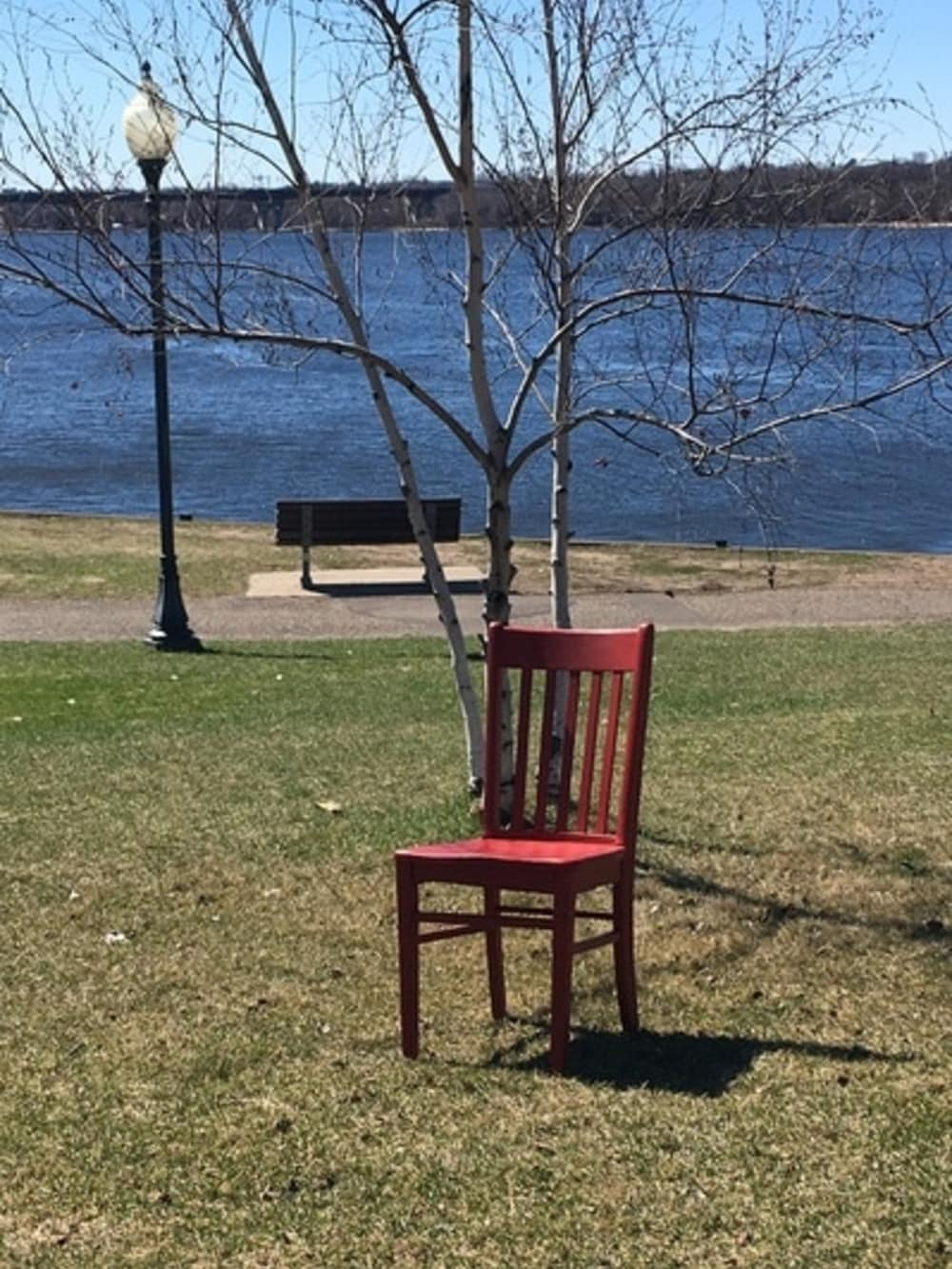 red chair sitting on shore along lake